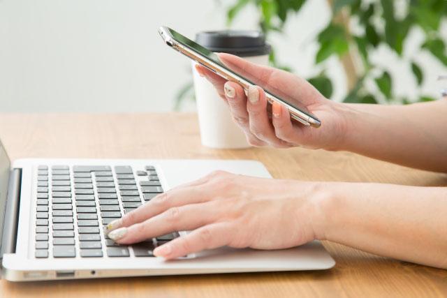 パソコンとスマホを持つ女性