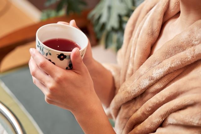マグカップでお茶を飲む女性